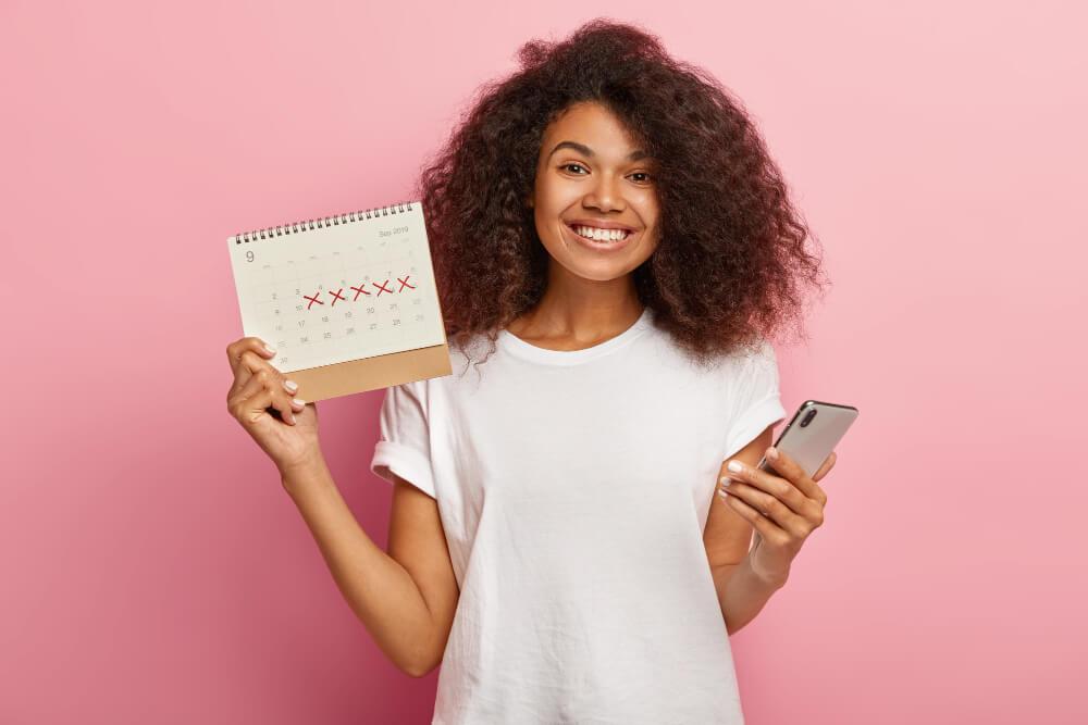 mujer sonriente de pelo rizado con remera blanca y fondo rosa con un calendario y celular en su mano