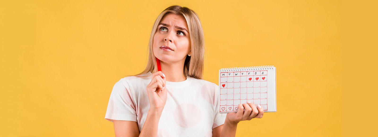 Mujer dubitativa con un calendario menstrual