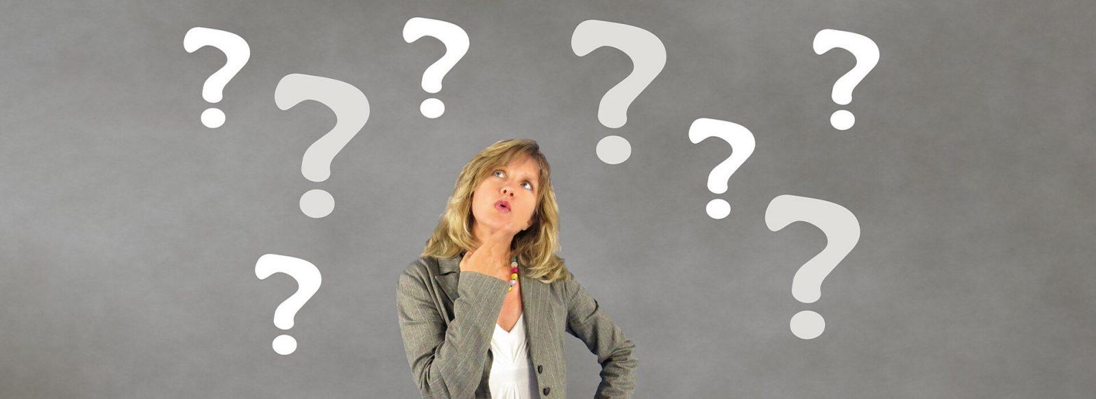 mujer rubia de saco gris y pantalón con signos de interrogación o pregunta en un fondo gris.