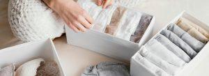 mujer ordenando ropa interior en cajas organizadoras